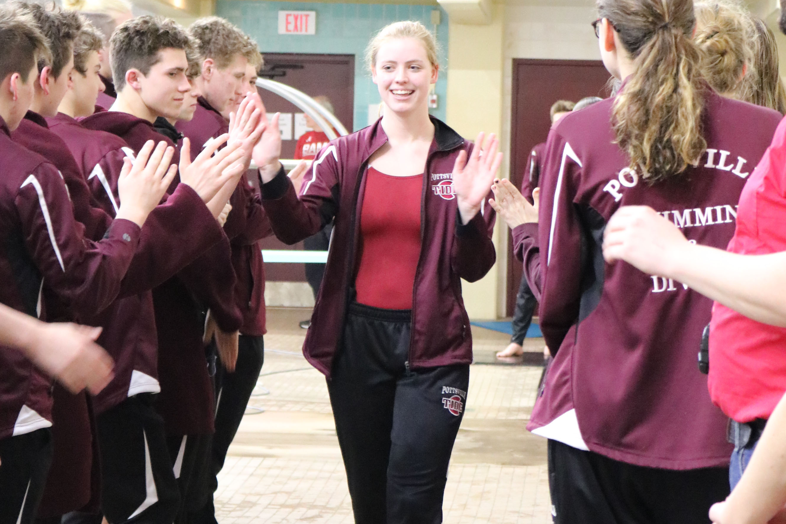 """Walking down the aisle aisle formed by her teammates, senior Sarah Corse-Campion receives high fives on senior night. Senior night was held January 31 against Mahanoy Area. """"I will miss everything about high school swimming, especially bonding with my best friends,"""" Corse-Campion said."""