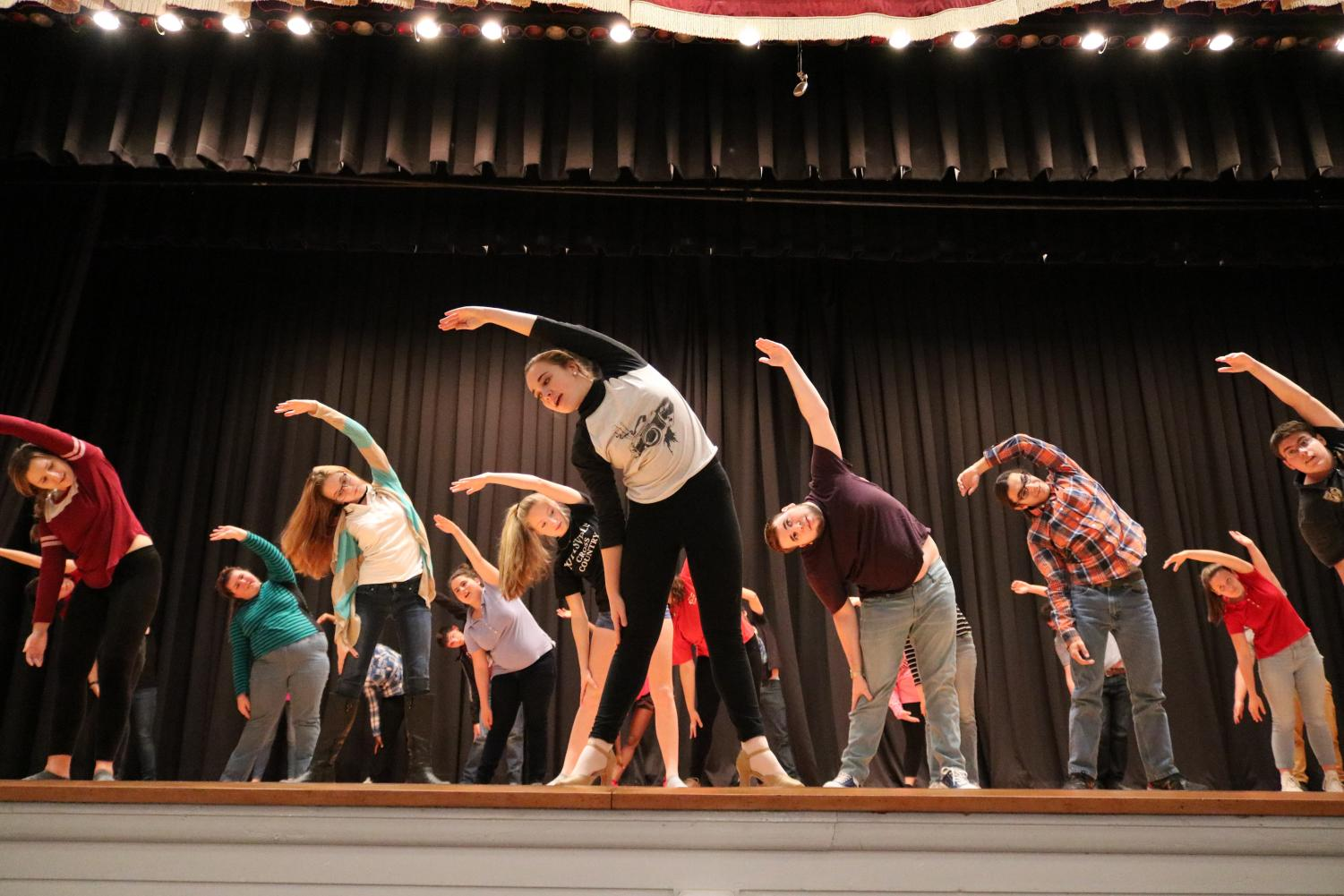 "Members of the Drama Club stretch before rehearsing for their musical. The Drama Club presented How to Succeed in Business Without Really Trying in March, and according to Mrs. Maria Malek, Drama Club adviser and English teacher, audience numbers are lower in years when the musical does not have high name recognition. ""Our audience numbers were not as high as they were in previous years,"" Mrs. Malek said."