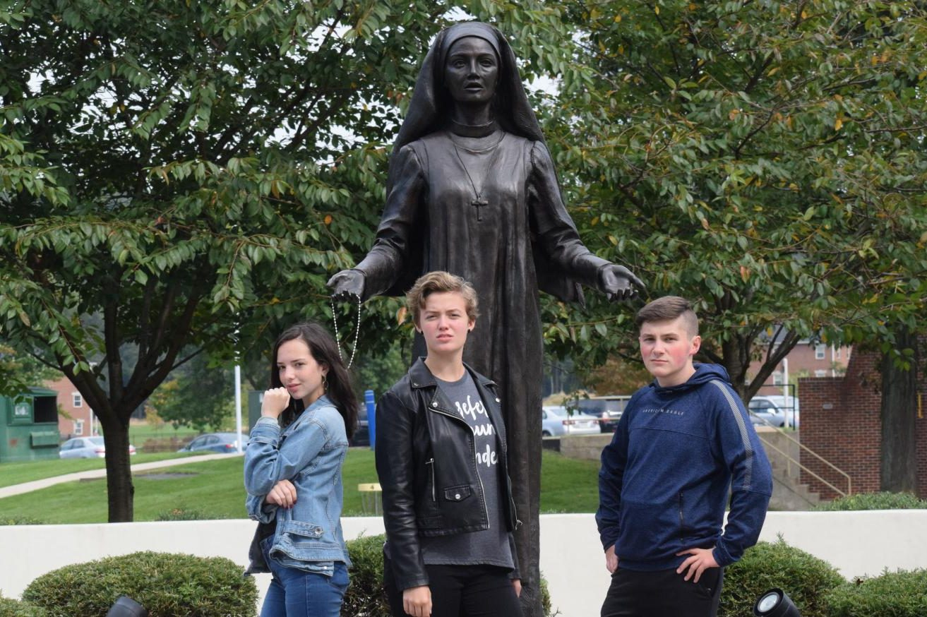 "In front of a statue of Jane Frances de Chantal, sophomores Lily McDonald, Kendra Speak, and Jake Montgomery pose for the camera. The Drama Club, Stage Crew, and Dramatic Literature class went on a field trip to DeSales University to watch a Shakespeare play. ""It was nice to see profesional actors so we can learn from them and do better. The show was good and fresh,"" Autumn McDonough, senior said."