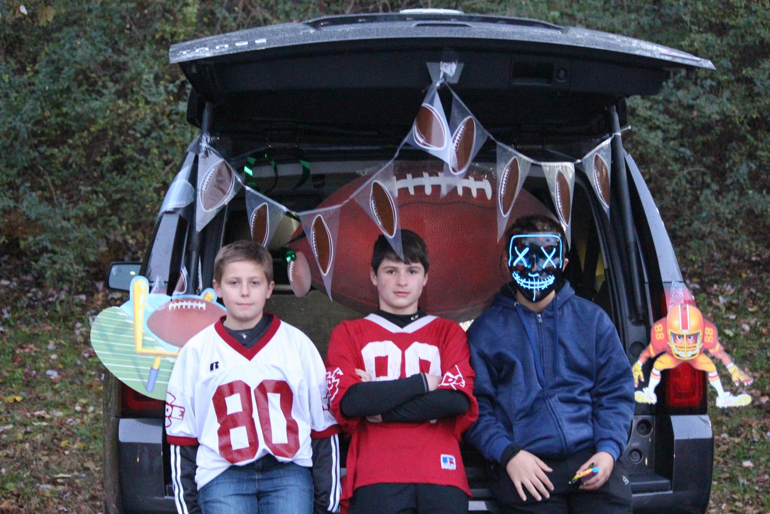 """Henry Mohl (middle) stands at his football themed vehicle. He said, """"This event is pretty cool and it's safer than normal trick-or-treating."""""""