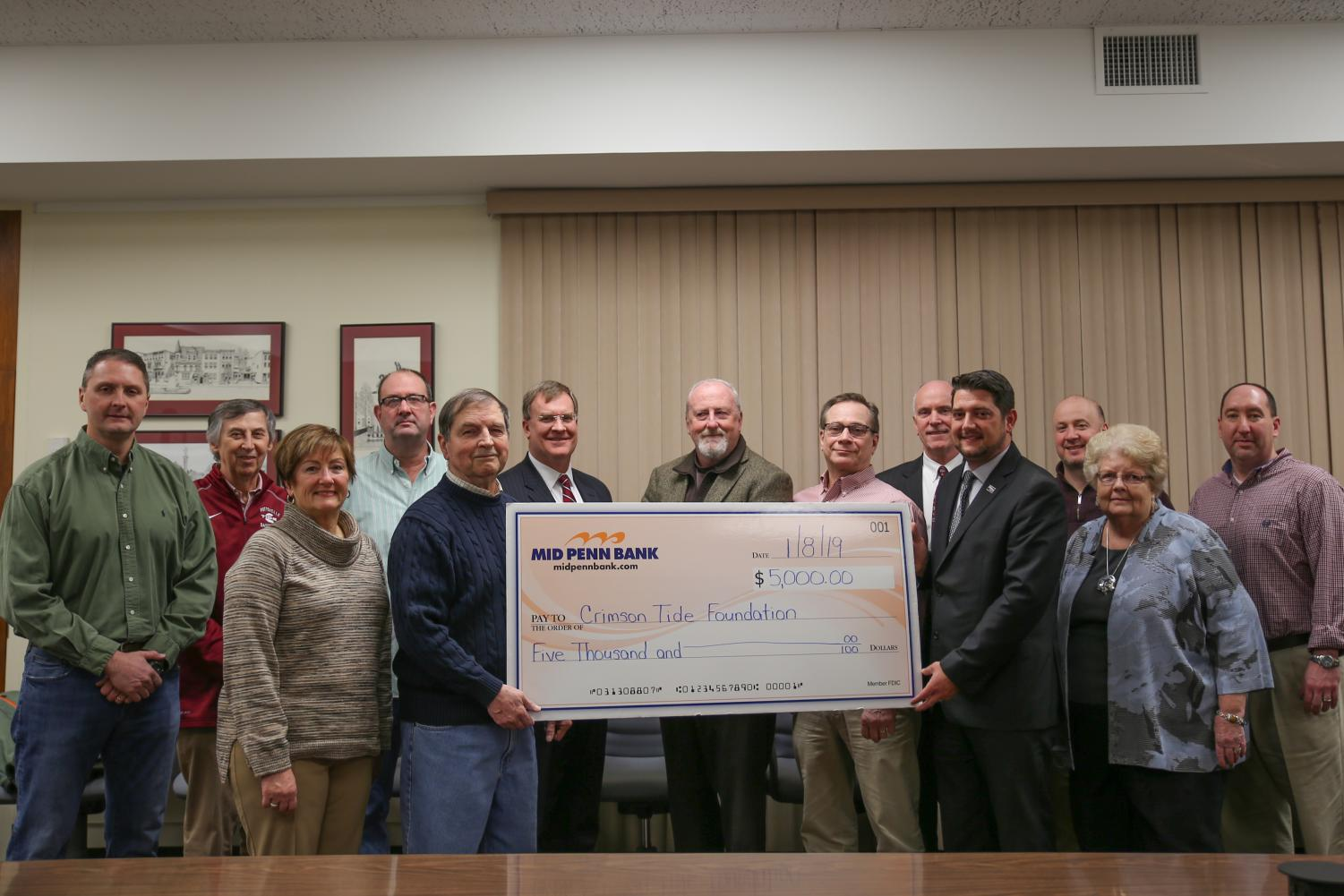 Members of the Crimson Tide Foundation pose with the $5,000 check from Mid Penn Bank. From left back row: Cory Holobetz, Ned Connors, Pete Joyce, Dr. Jeffrey Zwiebel, Craig Shields, Vince Wychunas, Jim Brennan of Mid Penn Bank, Adrian Portland, Bob Dusel Jr.—front row left Lillian Hobbs, John Liddle, Keith Kirby of Mid Penn Bank, Kathy Zwiebel