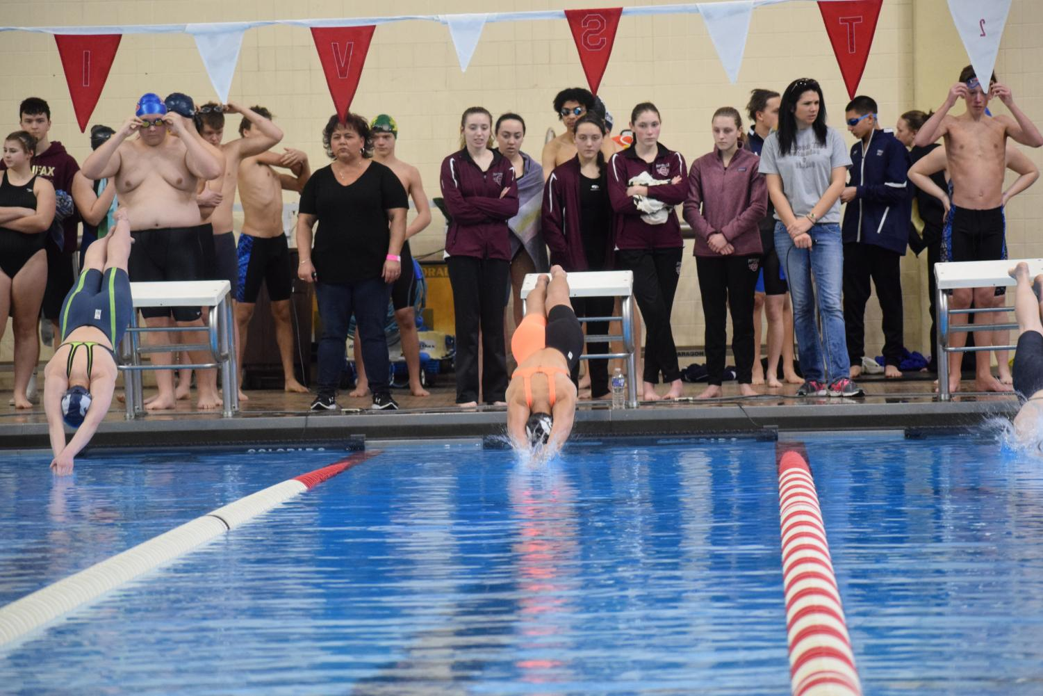 Senior Kylie Tohill (center) dives into the pool.
