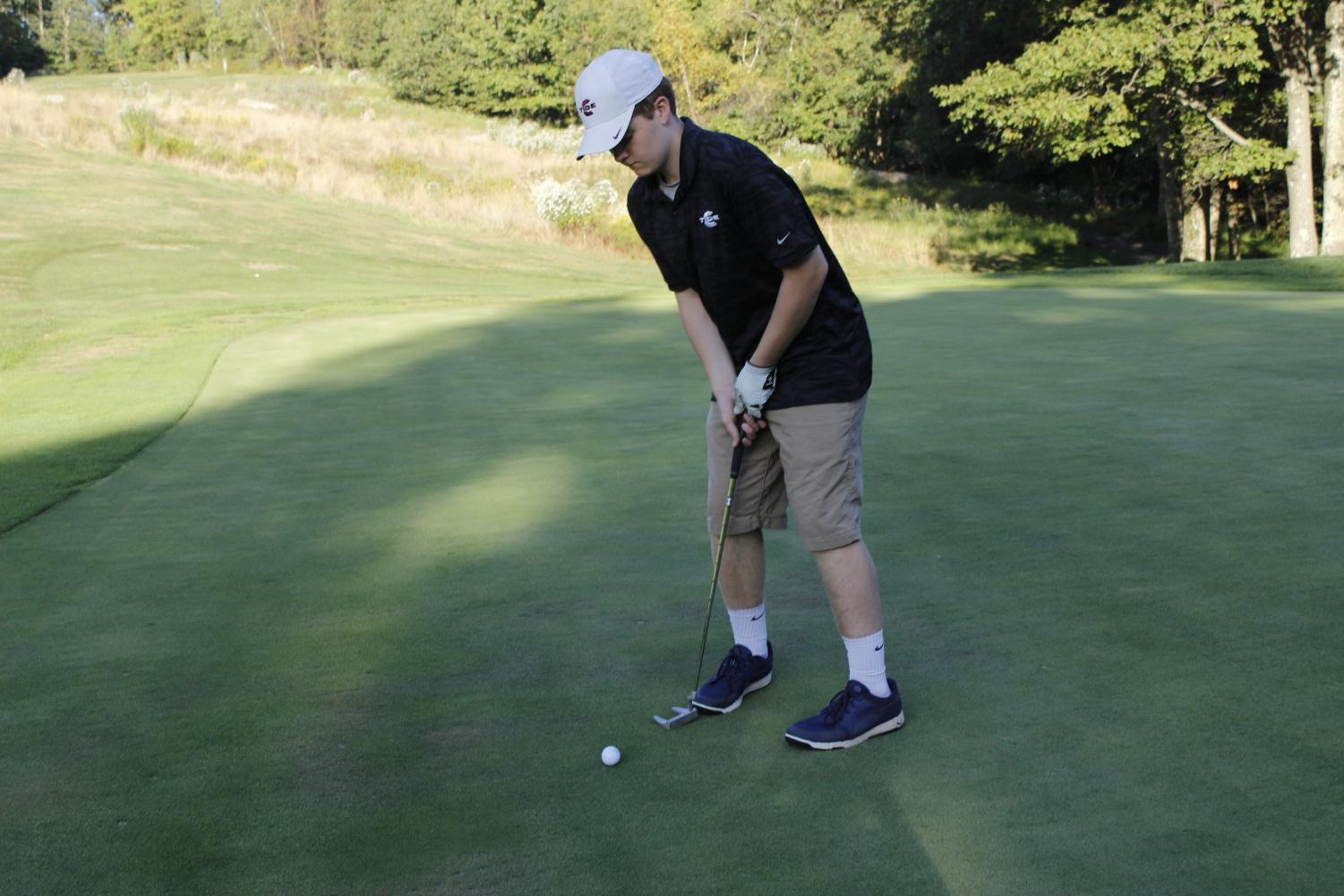 "Junior David Troutman is preparing to hit the ball. He wanted to make it into the hole to help his team. ""I want to focus and try my best on all 18 holes,"" said Troutman's teammate, Dominick Chiccini."