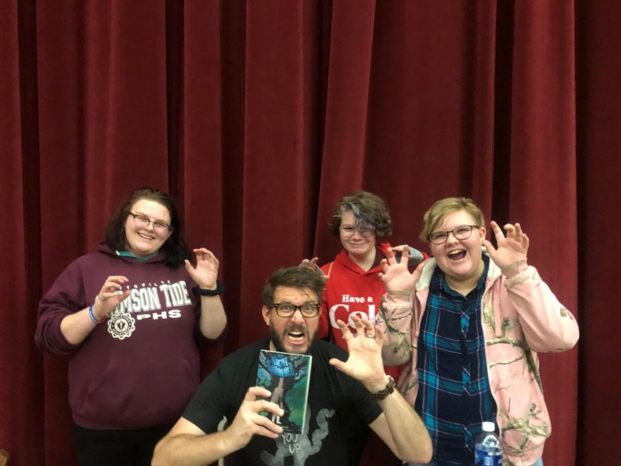 POSE+-+8th+graders+Madison+Auman%2C+Jaden+Ebert%2C+and+Catherine+Lubinsky+pose+with+author+Jonathan+Auxier+at+Teen+Library+Day+at+Kutztown+University.