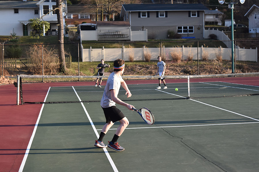 "Boys' tennis team members practice for their matches. They lost all of their matches so far but hope to turn things around. ""Our team could work on improving our defense, which I think is where we struggle the most,"" junior Jamie McCabe said."