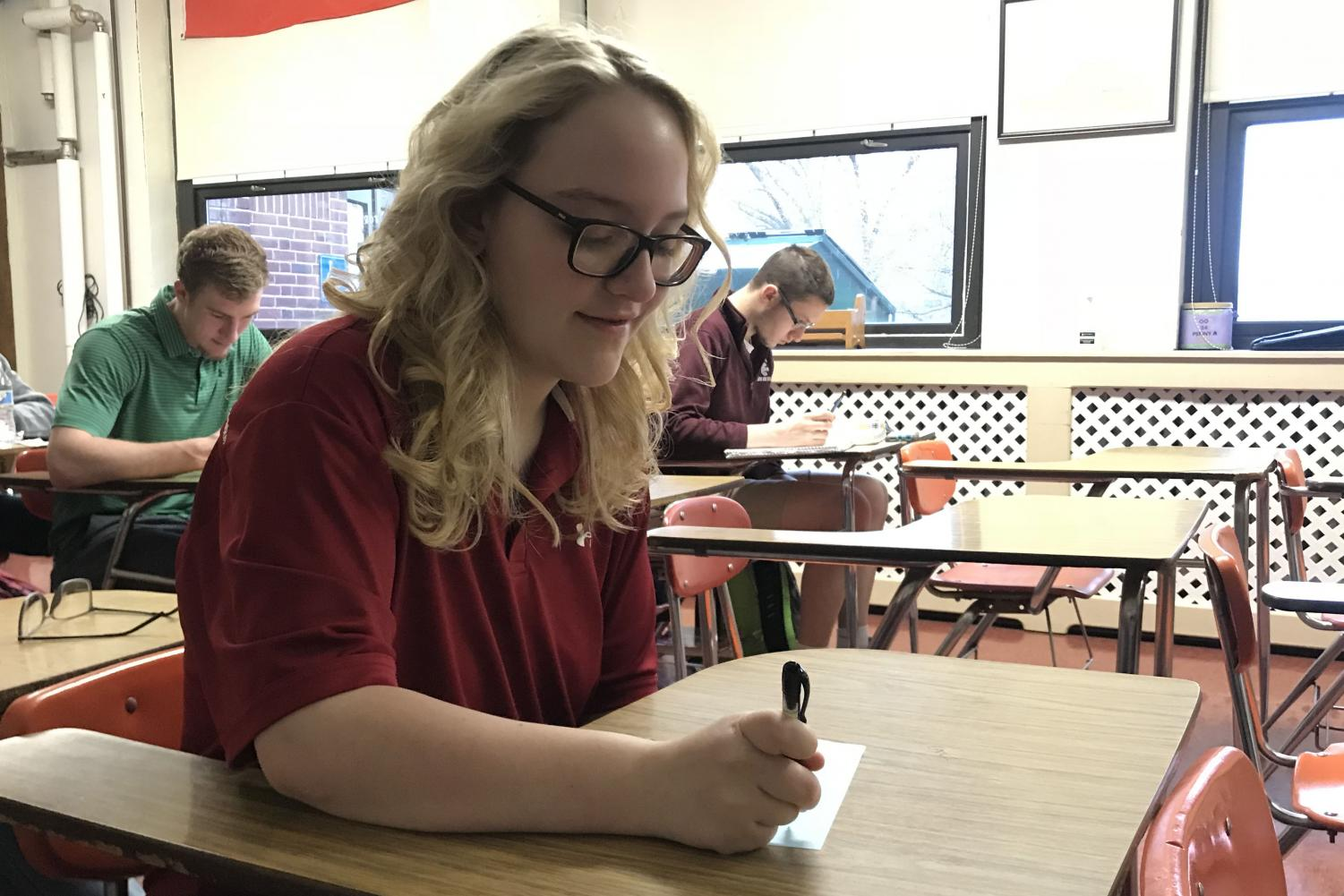 """THINK - While sitting in homeroom, senior Abby Wiederhold fills out a slip that instructed her to explain her favorite part of PAHS. The slips were distributed to each homeroom for students to fill out and were then hung up outside of Room 223 to showcase all the good students see in the school. """"I felt like this was a great initiative to promote positivity in our school,"""" Wiederhold said. """"Lately, there have been a lot of things that schools are trying to do in order to get students to be more comfortable and happy in their academic environments, so I thought this was a step in the right direction."""""""
