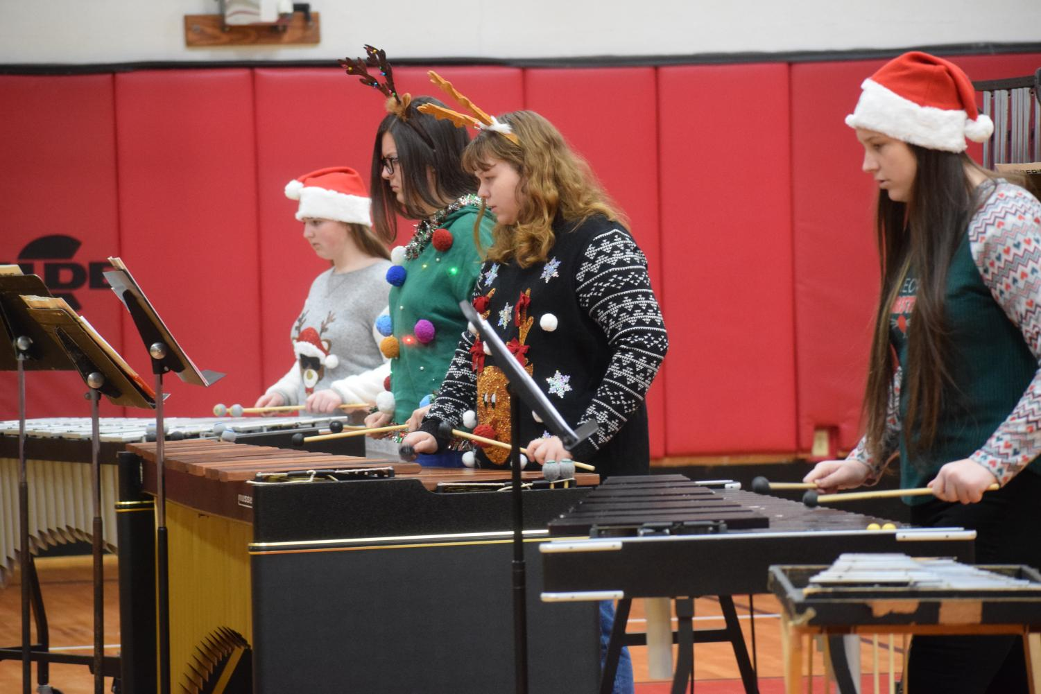 Victoria Oswald and musicians play for students at JSC. The ensemble members put on festive clothing and played Christmas music for third and fourth grade students. Junior Wesley Evans said,