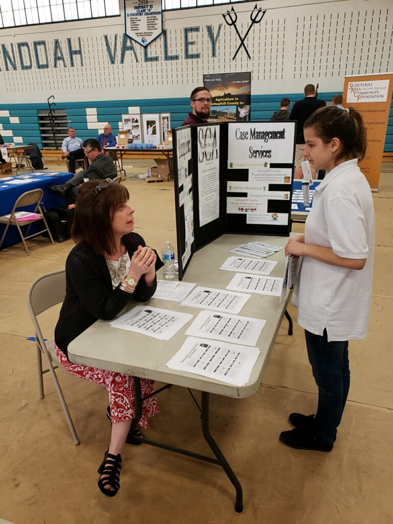 A Pottsville student learns about the Case Management Services while transition fair instructor talks to her.