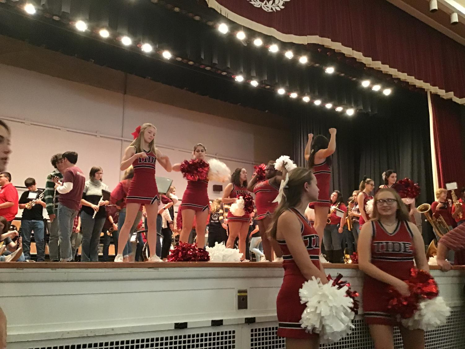 """Cheerleaders get ready to perform for the pep rally on stage in the auditorium. Tiana Green said, """" My favorite cheer we perform is of course everyone's favorite 'Give a Yell'. Everyone goes crazy and it's the best cheer around in my opinion""""."""